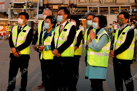 Secretary for Food and Health Sophia Chan Siu-chee, right, and Secretary for the Civil Service Patrick Nip Tak-kuen, second right, observe containers carrying Sinovac Biotech coronavirus disease (COVID-19) vaccines are unloaded from a Cathay Pacific Airways aircraft in Hong Kong