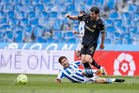 David Silva of Real Sociedad CF competes for the ball with Manuel Alejandro Garcia of Deportivo Alaves during the La Liga match between Real Sociedad CF and Deportivo Alaves at Reale Arena on February 21, 2021 in San Sebastian, Spain.