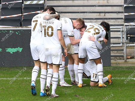 Charlie Brown of Milton Keynes Dons celebrates scoring his sides fourth goal with team-mates