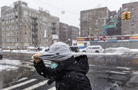 A person shields themselves from the snow and wind during a storm in New York, New York, USA, 19 February 2021. The storm, which has caused large widespread power outages in Texas and other parts of the United States, is expected to drop several inches of snow in the New York area and other parts of the Eastern Seaboard.