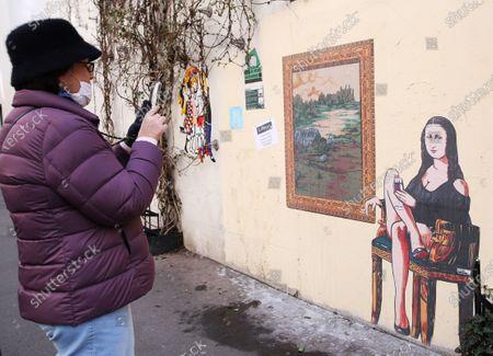 "A woman takes photos of a graffiti themed ""Mona Lisa"" (La Joconde) in Paris, France, Feb. 19, 2021."