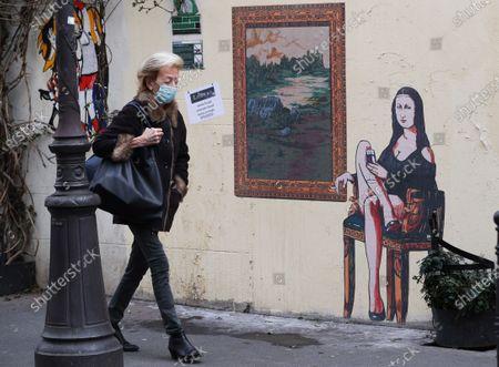 "A woman walks past a graffiti themed ""Mona Lisa"" (La Joconde) in Paris, France, Feb. 19, 2021."