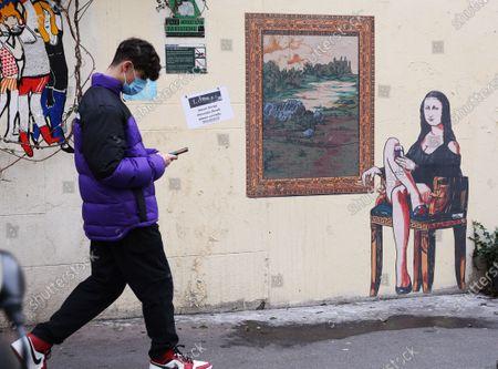 "A man walks past a graffiti themed ""Mona Lisa"" (La Joconde) in Paris, France, Feb. 19, 2021."