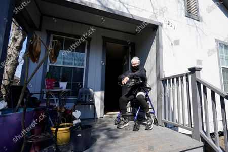 Nancy Wilson sits on her porch after returning from a water distribution site, in Houston. Wilson does not have full running water. The city remains under a boil water notice and many residents lack water at home due to frozen or broken pipes