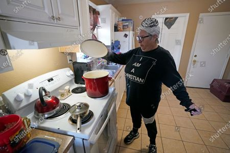 Stock Image of Nancy Wilson boils water in her home, in Houston. She does not have full running water as the city remains under a boil water notice and many residents lack water at home due to frozen or broken pipes