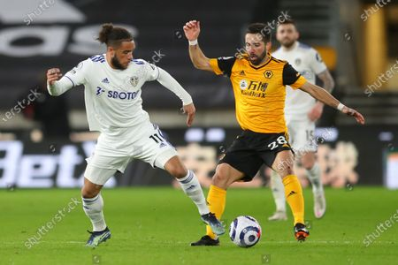 Leeds' Tyler Roberts (L) in action against Wolverhampton's Joao Moutinho (R) during the English Premier League soccer match between Wolverhampton Wanderers and Leeds United in Wolverhampton, Britain, 19 February 2021.