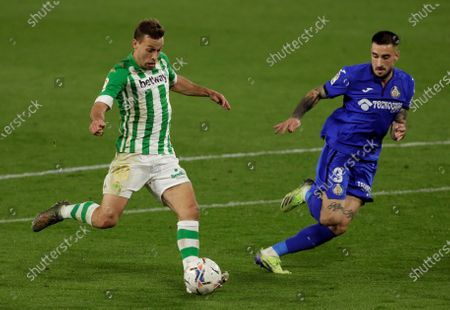 Betis' Sergio Canales (L) vies for the ball with Getafe's Erick Cabaco (R) during the Spanish LaLiga soccer match between Real Betis and Getafe CF held at Benito Villamarin stadium, in Seville, southern Spain, 19 February 2021.