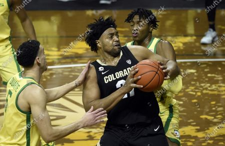 Colorado forward Evan Battey (21) spins toward the basket as he is guarded by Oregon guard Chris Duarte (5) and Oregon forward Chandler Lawson (13) during the first half of an NCAA college basketball game, in Eugene, Ore