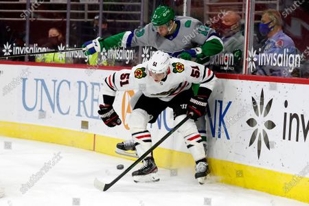 Carolina Hurricanes' Warren Foegele (13) collides with Chicago Blackhawks' Ian Mitchell (51) behind the net during the second period of an NHL hockey game in Raleigh, N.C
