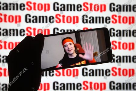 Keith Gill, known on Reddit under the pseudonym DeepFuckingValue and as Roaring Kitty, is seen on a fragment of a youtube video displayed on a smartphone screen in front of GameStop logo.