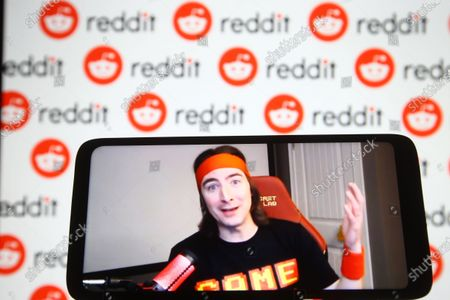 Keith Gill, known on Reddit under the pseudonym DeepFuckingValue and as Roaring Kitty, is seen on a fragment of a youtube video displayed on a smartphone screen in front of Reddit logo.