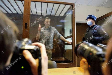 Russian opposition leader Alexei Navalny stands in a cage in the Babuskinsky District Court in Moscow, Russia, . Two trials against Navalny are being held Moscow City Court one considering an appeal against his imprisonment in the embezzlement case and another announcing a verdict in the defamation case