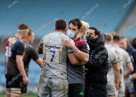 Stock Photo of Scott Baldwin of Harlequins hugs Jono Ross of Sale Sharks after the final whistle while wearing a surgical mask; Twickenham Stoop, London, England; English Premiership Rugby, Harlequins versus Sale Sharks.