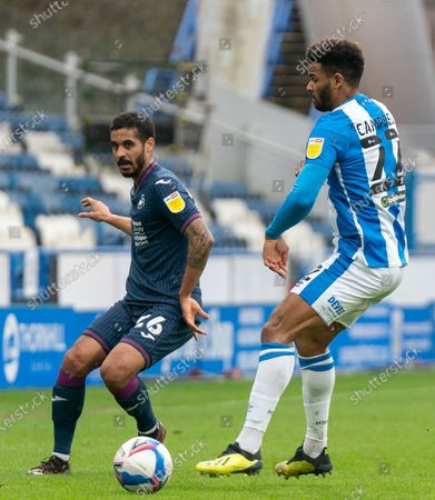 Kyle Naughton of Swansea City plays a pass down the line past Fraizer Campbell; The John Smiths Stadium, Huddersfield, Yorkshire, England; English Football League Championship Football, Huddersfield Town versus Swansea City.