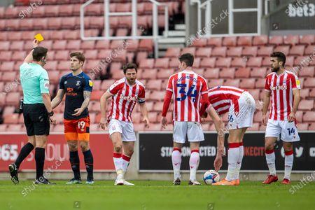 James Collins of Luton Town receives a yellow card; Bet365 Stadium, Stoke, Staffordshire, England; English Football League Championship Football, Stoke City versus Luton Town.
