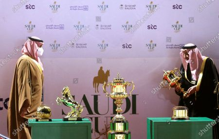 Stock Picture of Saudi Crown Prince Mohammed bin Salman wears a face mask to help curb the spread of the coronavirus as he awards Prince Abdel Rahman bin Abdullah al Faisal, right, the owner of the winner horse of the Saudi Cup $20 million award at King Abdul Aziz race track in Riyadh, Saudi Arabia