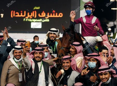 Irish jockey David Egan celebrates with the family of Prince Abdel Rahman bin Abdullah al Faisal, the owners of the winning horse of the Saudi Cup $20 million award at King Abdul Aziz race track in Riyadh, Saudi Arabia