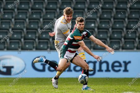 Charlie Atkinson of Wasps kicks past Richard Wigglesworth of Leicester Tigers