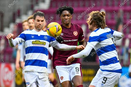 Kyle Jacobs (#6) of Greenock Morton FC, Armand Gnanduillet (#9) of Heart of Midlothian FC and Robbie Muirhead (#9) of Greenock Morton FC watch the ball during the SPFL Championship match between Heart of Midlothian and Greenock Morton at Tynecastle Park, Edinburgh