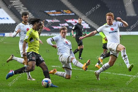 Milton Keynes Dons defender Dean Lewington (3) and Milton Keynes Dons forward Charlie Brown (11) leap in to stop a cross from Northampton Town defender (on loan from Luton Town) Peter Kioso (15)  during the EFL Sky Bet League 1 match between Milton Keynes Dons and Northampton Town at stadium:mk, Milton Keynes