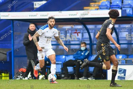 Stock Picture of Tranmere Rovers striker Kaiyne Woolery (14) dribbles at Oldham Athletic's defender Sido Jombati (4) during the EFL Sky Bet League 2 match between Tranmere Rovers and Oldham Athletic at Prenton Park, Birkenhead