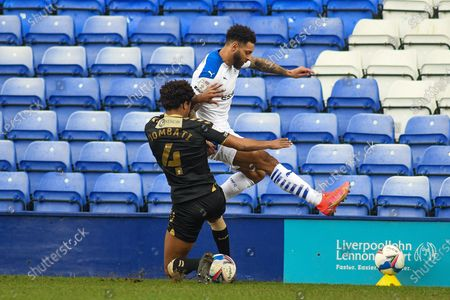 Stock Photo of Oldham Athletic's defender Sido Jombati (4) challenges Tranmere Rovers striker Kaiyne Woolery (14) during the EFL Sky Bet League 2 match between Tranmere Rovers and Oldham Athletic at Prenton Park, Birkenhead