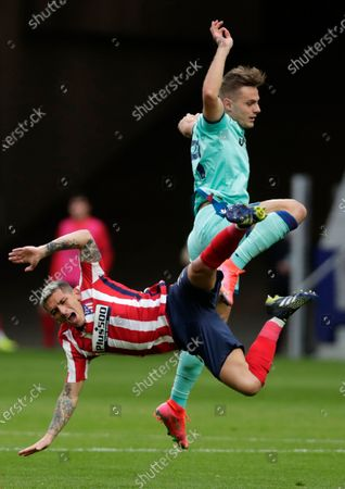 Atletico Madrid's Lucas Torreira, left, fights for the ball with Levante's Oscar Duarte during the Spanish La Liga soccer match between Atletico Madrid and Levante at the Wanda Metropolitano stadium in Madrid, Spain