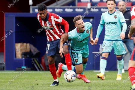 Atletico Madrid's Thomas Lemar (L) in action against Levante's Daniel Gomez (C) during the Spanish La Liga soccer match between Atletico Madrid and Levante UD in Madrid, Spain, 20 February 2021.