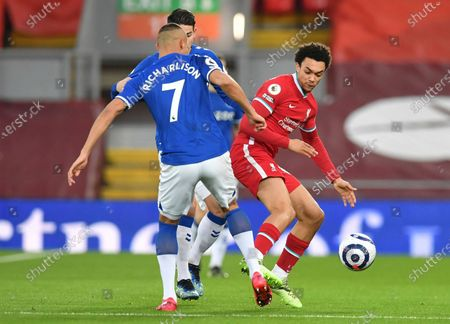 Liverpool's Trent Alexander-Arnold. Right vies for the ball with Everton's Richarlison during the English Premier League soccer match between Liverpool and Everton at Anfield in Liverpool, England