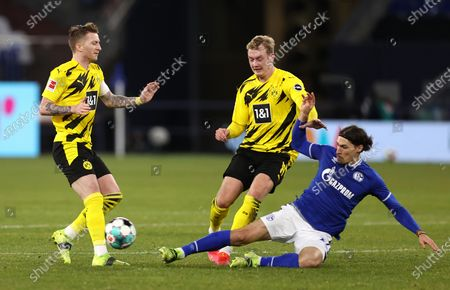 Julian Brandt (C) of Dortmund in action against Benjamin Stambouli (R) of Schalke during the German Bundesliga soccer match between FC Schalke 04 and Borussia Dortmund in Gelsenkirchen, Germany, 20 February 2021.