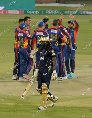 Stock Picture of Quetta Gladiators Chris Gayle, front, walks back, while Karachi Kings players celebrate his dismissal during a Pakistan Super League T20 cricket match between Karachi Kings and Quetta Gladiators at National Stadium, in Karachi, Pakistan