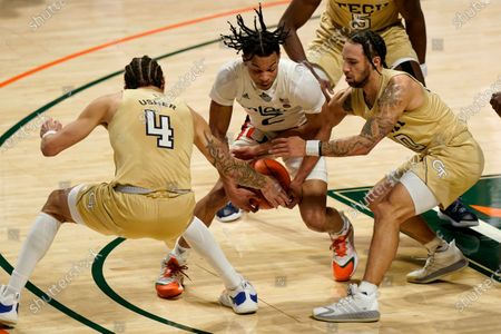 Georgia Tech guard Jordan Usher (4) and guard Jose Alvarado, right, defend against Miami guard Isaiah Wong during the first half of an NCAA college basketball game, in Coral Gables, Fla