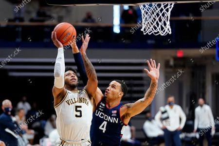 Villanova's Justin Moore (5) goes up for a shot against Connecticut's Tyrese Martin (4) during the first half of an NCAA college basketball game, in Villanova, Pa