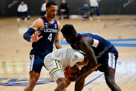 Villanova's Justin Moore, center, tries to hang to the ball against Connecticut's Adama Sanogo, right, and Tyrese Martin during the first half of an NCAA college basketball game, in Villanova, Pa
