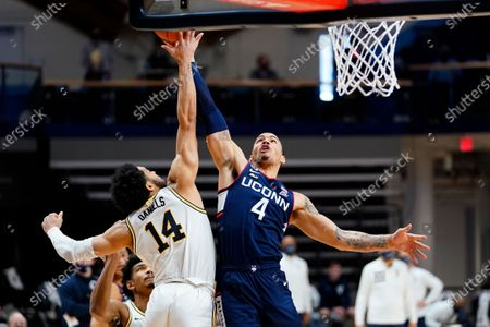 Connecticut's Tyrese Martin (4) goes up for a shot against Villanova's Caleb Daniels (14) during the second half of an NCAA college basketball game, in Villanova, Pa
