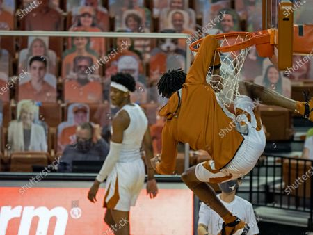 Texas forward Greg Brown hangs from the rim after making a dunk during warmups before an NCAA college basketball game between Texas and West Virginia, in Austin, Texas