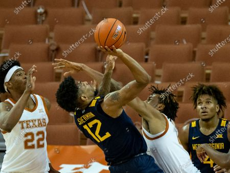 West Virginia guard Taz Sherman (12) puts up a shot against Texas forward Greg Brown during the second half of an NCAA college basketball game, in Austin, Texas. West Virginia won 84-82