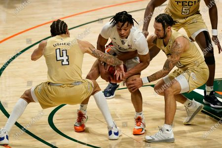 Georgia Tech guard Jordan Usher (4) and guard Jose Alvarado, right, defend Miami guard Isaiah Wong during the first half of an NCAA college basketball game, in Coral Gables, Fla