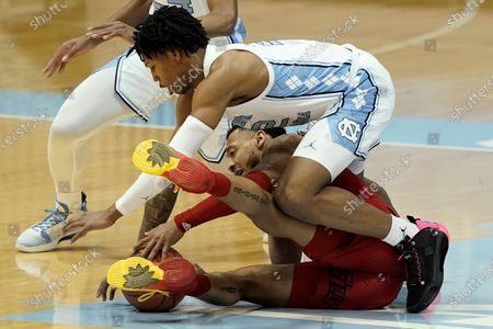 North Carolina guard Caleb Love, top, and Louisville guard Carlik Jones reach for the ball during the first half of an NCAA college basketball game in Chapel Hill, N.C