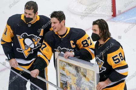 Pittsburgh Penguins' Sidney Crosby, center, poses with Evgeni Malkin, left, and Kris Letang during a ceremony honoring his 1000th NHL hockey game with the team before an NHL hockey game against the New York Islanders, in Pittsburgh
