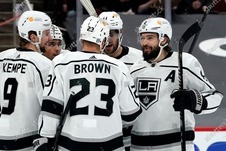 Los Angeles Kings defenseman Drew Doughty (8), center Anze Kopitar (11), right wing Dustin Brown (23), and right wing Adrian Kempe (9) celebrates a goal by Kings right wing Alex Iafallo, back left, against the Arizona Coyotes during the second period of an NHL hockey game, in Glendale, Ariz
