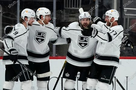 Los Angeles Kings center Gabriel Vilardi, second from left, celebrates his goal against the Arizona Coyotes with Kings center Jeff Carter (77), defenseman Drew Doughty (8), and right wing Adrian Kempe (9) during the third period of an NHL hockey game, in Glendale, Ariz