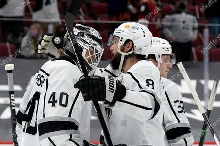 Los Angeles Kings goaltender Calvin Petersen (40) is congratulated by Kings defenseman Drew Doughty (8) as Kings defenseman Tobias Bjornfot (33) celebrates with other teammates after the third period of an NHL hockey game against the Arizona Coyotes, in Glendale, Ariz