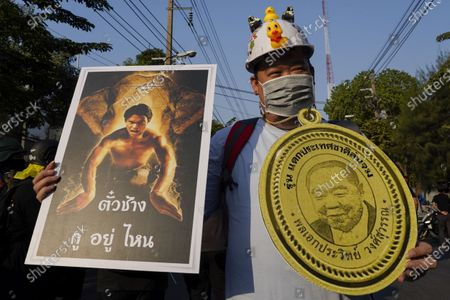 """A protestor holds a poster of Tony Jaa in Tom-Yum-Goong movie (left) with his catchphrase in the movie is """"where is my elephant?"""" which is a parody of """"Elephant Ticket"""" a fast track lane for promotions that cut through the entire structure of the police force, this scandal was revealed at no-confidence recently and a picture of General Prawit Wongsuwan (right) during the demonstration Pro-democracy protesters demonstrate demanding the prime minister to resign, reforms the monarchy and release every prisoner under article 112 or lesse majeste law outside the Thai parliament building in Bangkok."""