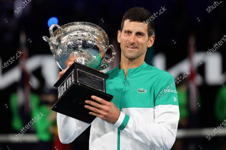 1st seed Novak Djokovic of Serbia poses for photographs with the trophy defeating 4th seed Daniil Medvedev of the Russian Federation in the Men's Final match match on day 14 of the Australian Open on Rod Laver Arena, in Melbourne, Australia