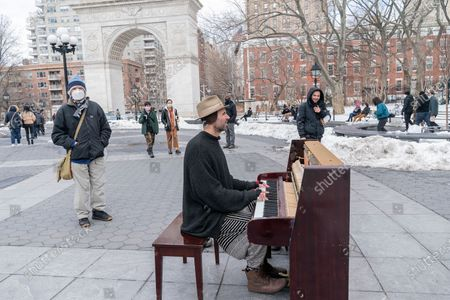 Stock Photo of Street Musician Andrew Kalleen plays piano in cold weather on Washington Square Park