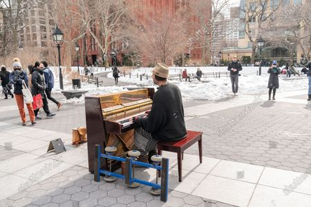 Stock Picture of Street Musician Andrew Kalleen plays piano in cold weather on Washington Square Park