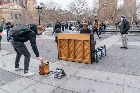 A man gives donation to street nusician Andrew Kalleen playing piano in cold weather on Washington Square Park.
