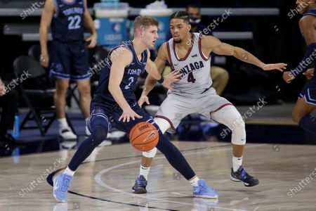 San Diego guard Joey Calcaterra, left, handles the ball while pressured by Gonzaga guard Aaron Cook during the second half of an NCAA college basketball game in Spokane, Wash