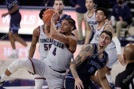 Gonzaga guard Aaron Cook (4) grabs a rebound next to San Diego forward Yavuz Gultekin (11) during the second half of an NCAA college basketball game in Spokane, Wash